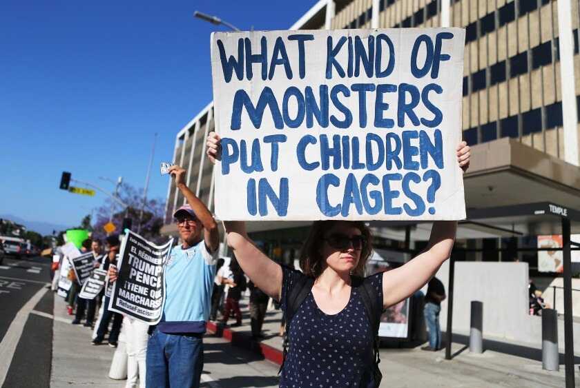 "A protester outside L.A. federal building two years ago holds a sign reading, ""What kind of monsters put children in cages?"""
