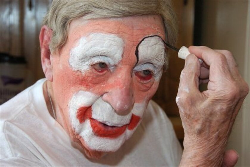 """In this March 29, 2012, photo, Floyd """"Creeky"""" Creekmore puts on his makeup before a visit with children at a circus in Billings, Mont. Guinness World Records has anointed the world's oldest performing clown, and it's none other than Creekmore, a former Montana rancher who's been donning the big nose and bright makeup for almost eight decades. (AP Photo/Matthew Brown)"""