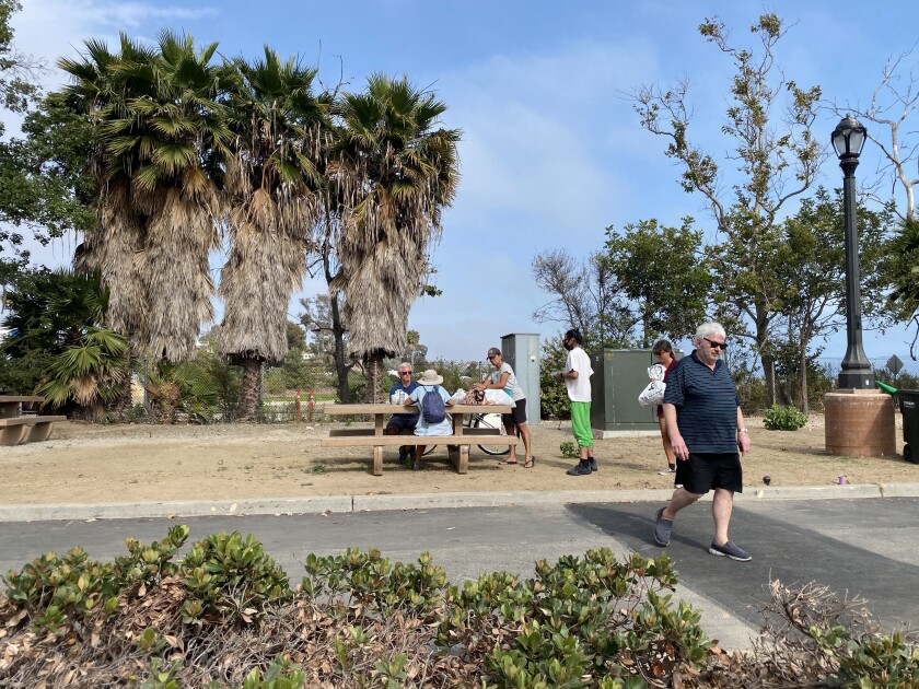 Volunteer Jan Greenberg walks back to the food set up after assisting men at the table at Doheny State Beach on June 16.