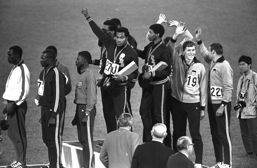 Lee Evans, center, holds up a fist after receiving a gold medal at the Mexico City Games in 1968.