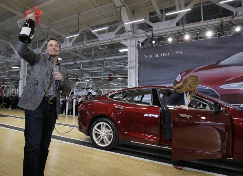 FILE - In this June 22, 2012 file photo, Tesla Motors Inc. CEO Elon Musk holds up a bottle of wine given as a gift from one of their first customers, right, during a rally at the Tesla factory in Fremont, Calif. Tesla Motors says it is preparing a site near Reno, Nevada, as a possible location for