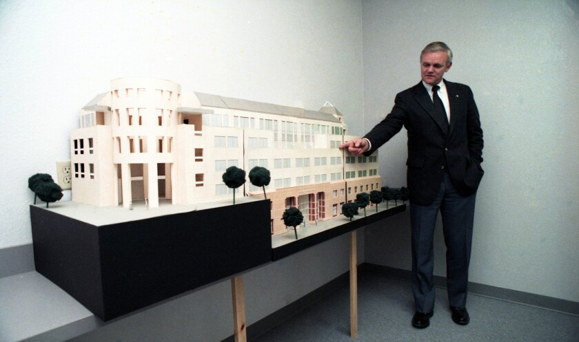 Bill Stacy, president of CSU San Marcos, shows model of one of the planned campus buildings in February 1990.