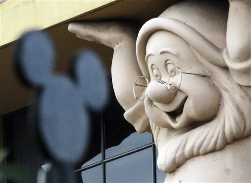 FILE - In this Nov. 12, 2009 file photo, a smiling Doc, one of the Seven Dwarfs from the 1930s Disney classic animated feature, is seen on a building behind a stylized Mickey Mouse figure on a fence at Walt Disney Co. corporate headquarters in Burbank, Calif. Disney Co. releases quarterly financial results after the market close Tuesday, Feb. 9, 2010. (AP Photo/Reed Saxon, File)