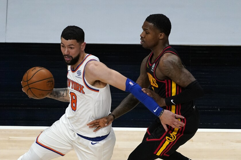 New York Knicks guard Austin Rivers (8) drives against Atlanta Hawks guard Brandon Goodwin (0) during the first half of an NBA basketball game Monday, Jan. 4, 2021, in Atlanta. (AP Photo/John Bazemore)