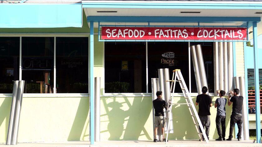 Workers install hurricane shutters on a restaurant in Islamorada in the Florida Keys.