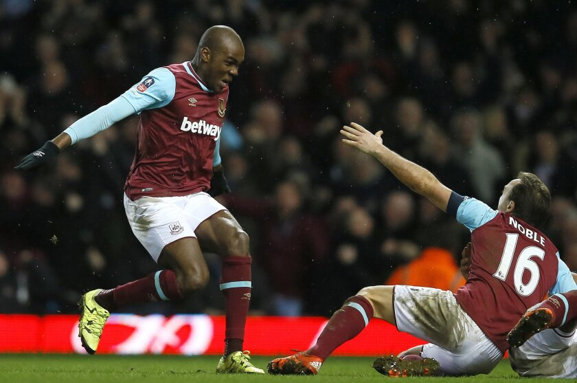 West Ham's Angelo Ogbonna, left, celebrates scoring the winning goal during the English FA Cup fourth round replay soccer match between West Ham United and Liverpool at the Boleyn Ground stadium in London, Tuesday, Feb. 9, 2016. (AP Photo/Kirsty Wigglesworth)