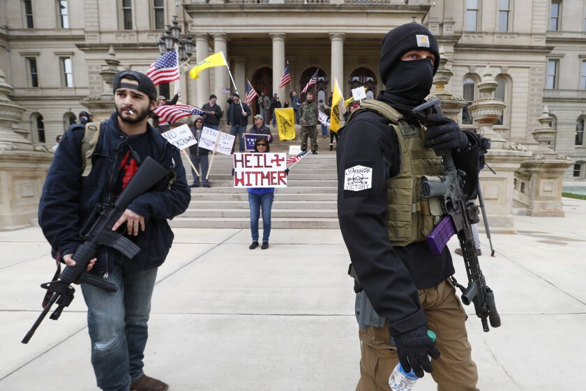 FILE - In this April 15, 2020, file photo, protesters carry rifles near the steps of the Michigan State Capitol building in Lansing, Mich. When President Trump-supporting insurrectionists stormed the U.S. Capitol in an attempt to overturn the presidential election on Wednesday, Jan. 6 2021 the nation was shocked, but not unwarned. A series of dress rehearsals of sorts have played out in statehouses in Michigan, Oregon, Idaho and elsewhere in recent months, with armed protesters forcing their way into buildings. (AP Photo/Paul Sancya, File)