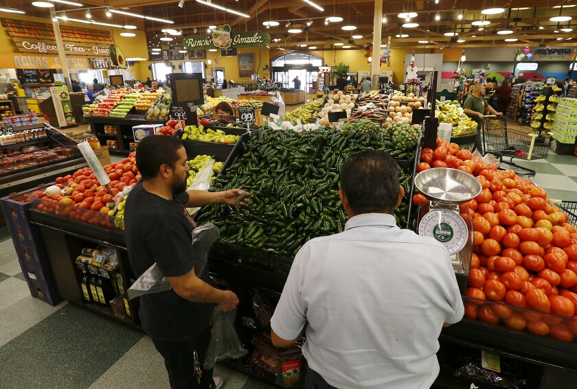 Customers pick out jalapeño peppers at Northgate