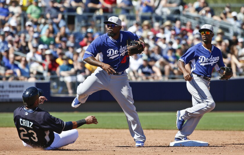 Howie Kendrick makes a relays throw to first base from shortstop Jimmy Rollins as Seattle's Nelson Cruz slides in to second base during a game March 15.