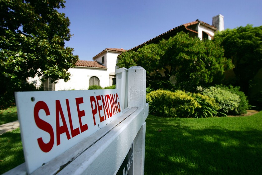 """A """"Sale Pending"""" sign is in front of a house"""