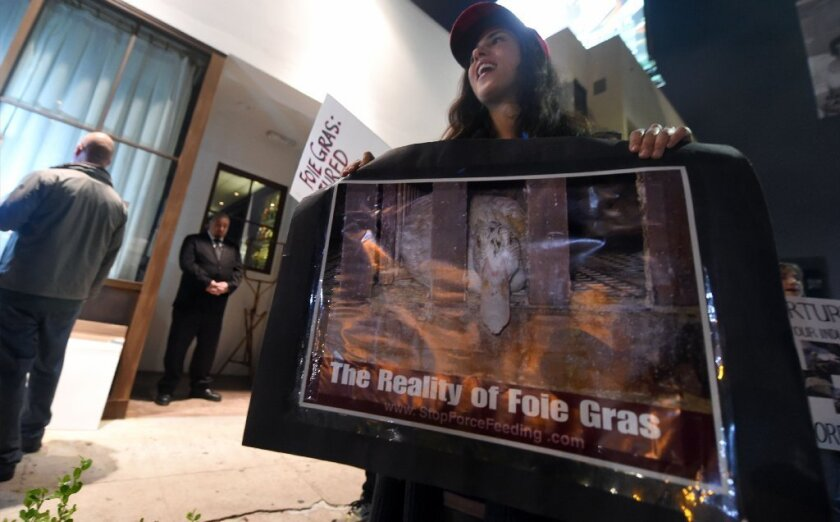 Activists hold placards and shout slogans while gathered outside a restaurant serving foie gras in Beverly Hills.