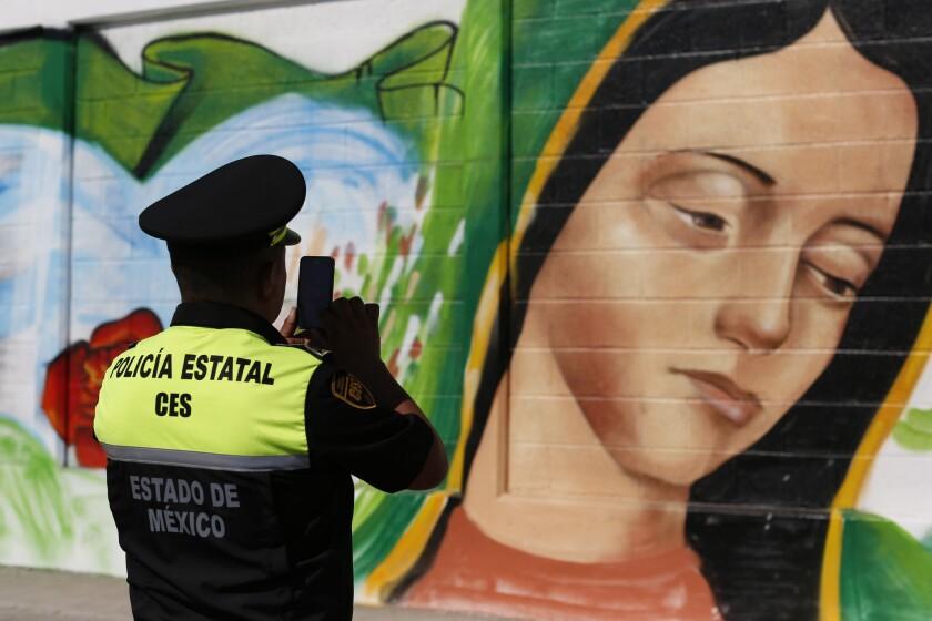 Un policía toma una foto de un mural de la Virgen de Guadalupe en el barrio de Ecatepec de la Ciudad de México. El papa visitará la Basílica de la Virgen de Guadalupe durante su viaje a México. (AP Photo/Dario Lopez-Mills, File)