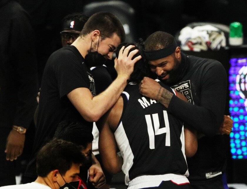Clippers guard Terance Mann is hugged by teammates Ivica Zubac, left, and DeMarcus Counsins, right.