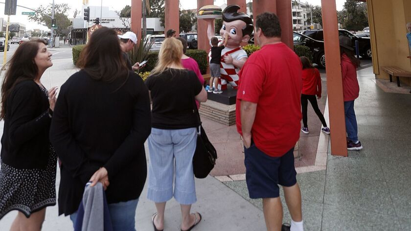 People gather around the Big Boy statue in front of the Bob's Big Boy restaurant to take photos of t