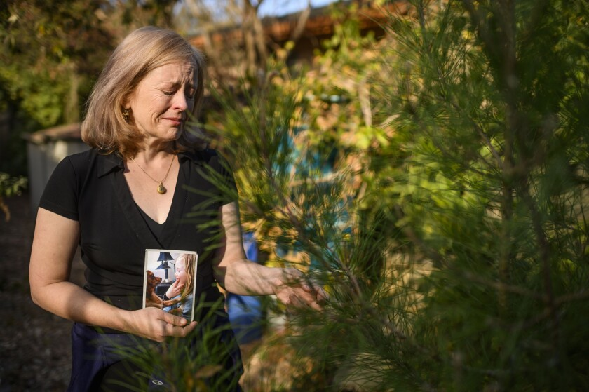 In this Sunday, Nov. 10, 2019, photo, Stacia Langley holds a photo of her late son, Max Benson, next to a tree he grew from a seed in his grandfather's backyard in Davis, Calif. Two private school administrators and a teacher are facing criminal charges in the death of Benson, an autistic student who was restrained for nearly two hours, prosecutors in Northern California said. (Daniel Kim/The Sacramento Bee via AP)