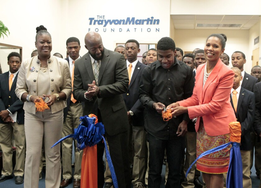 The parents and brother of Trayvon Martin — Sybrina Fulton, left, Tracy Martin and Jahvaris Fulton — along with Florida Memorial University President Roslyn Clark Artis, right, during a recent ribbon-cutting ceremony marking the launch of the Trayvon Martin Foundation last month.