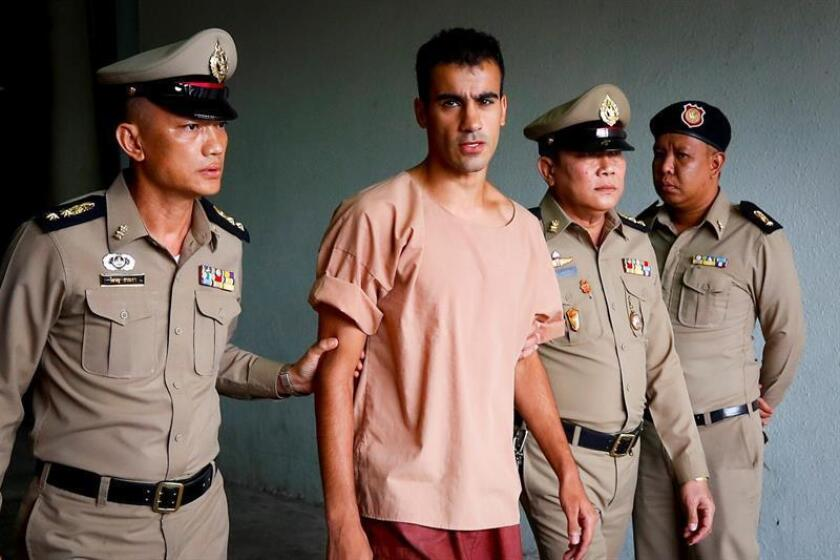 El futbolista y refugiado bareiní Hakeem Al Araibi es escoltado por dos funcionarios de prisiones tailandeses tras asistir a una vista de su proceso de extradición ante el Tribunal Criminal este lunes en Bangkok (Tailandia). EFE