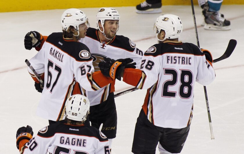 Anaheim Ducks' Matt Beleskey, center, celebrates with teammates Rickard Rakell, left, and Mark Fistric after scoring a goal against the San Jose Sharks during the third period of a preseason NHL hockey game, Saturday, Sept. 27, 2014, in San Jose, Calif. Ducks' Kevin Gagne is in the foreground. (AP Photo/George Nikitin)