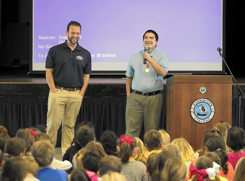Principal Todd Schmidt, left, and Special Olympic athlete Joseph Gorin laugh as students at Harbor View Elementary School ask questions of the four-time medalist during assembly on Monday. Newport Beach will be the host city for the 2015 Special Olympics to be held this summer.