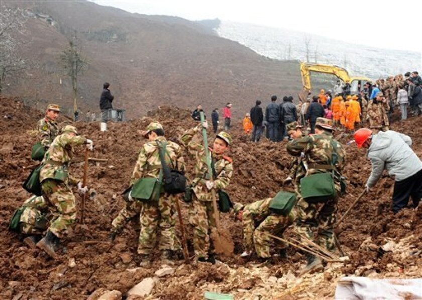 In this Jan. 11, 2013 photo provided by China's Xinhua News Agency, rescuers work at the mud-inundated debris after a landslide hit a village in Zhenxiong County, southwest China's Yunnan Province. (AP Photo/Xinhua, Shi Shengming)
