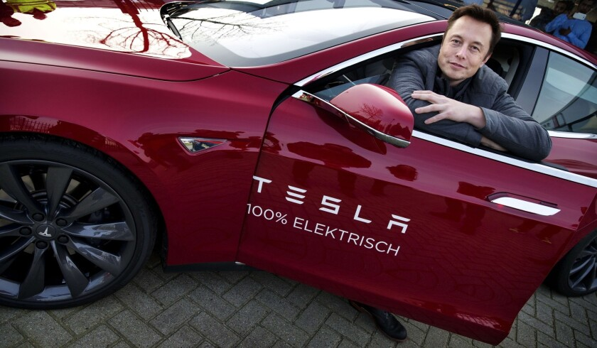 Elon Musk, co-founder and CEO of American electric vehicle manufacturer Tesla Motors, poses with a Tesla during a visit to Amsterdam.