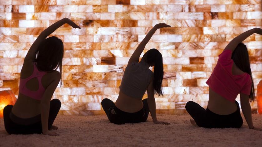 Women practice yoga in front of a wall of Himalayan salt at Salt Room LV, a new facility in Las Vegas that offers salt therapy.