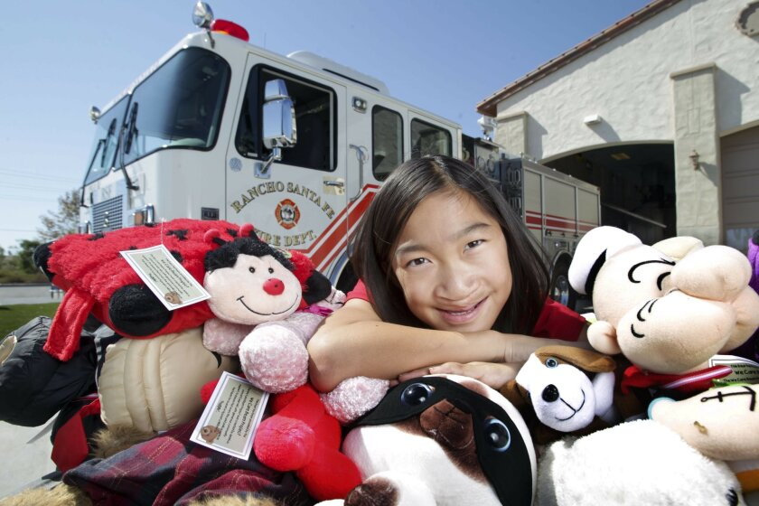 Monterey Ridge Elementary School fifth grader Jessica Carscadden, 10, with some of the donated stuffed animals, that she collected through a program she started at her school, while at the Rancho Santa Fe Fire Station 2 in 4S Ranch on Tuesday. Jessica has won a $50,000 Peace First prize for collect