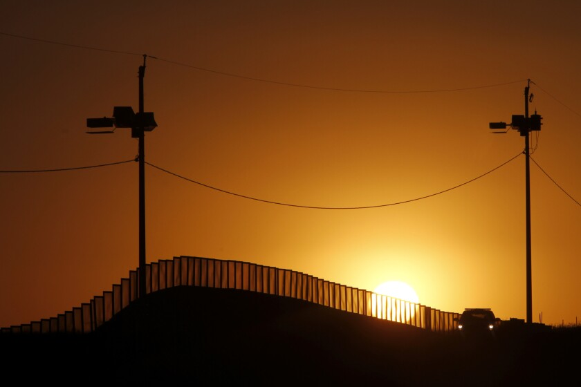 A Border Patrol vehicle cruises the U.S.-Mexico border fence in Naco, Ariz.