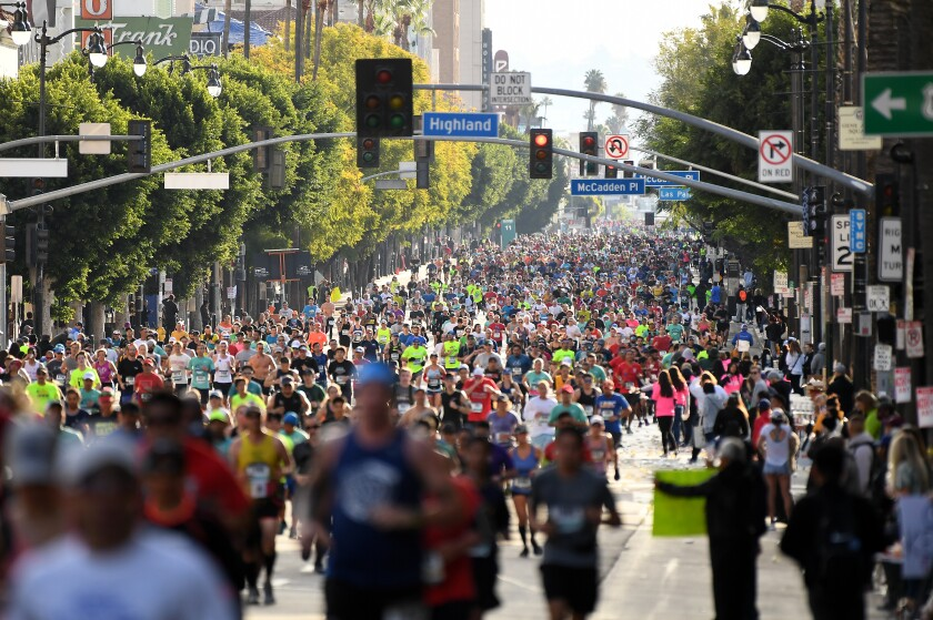 Runners jog along Hollywood Boulevard on Sunday during the Los Angeles Marathon.