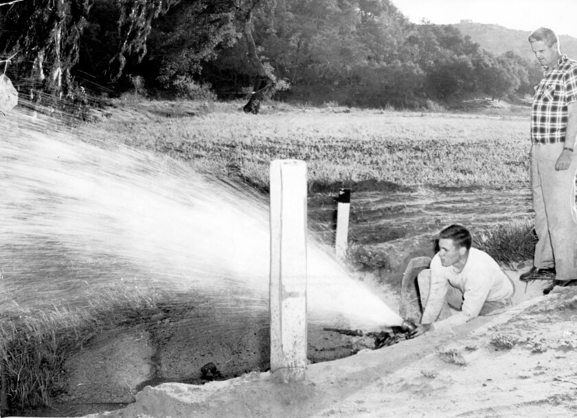 Les Berglulnd, the first Poway Municipal Water District employee, and Dave Shepardson, PMWD board member and Mary Shepardson's father, in 1954 on the then-Lewellen property turning the aqueduct water on for the first time.