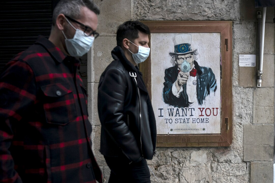 People walk past a poster by artist Tvboy amid a lockdown in Barcelona.