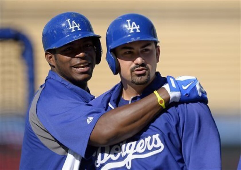 Los Angeles Dodgers' Yasiel Puig, left, hugs Adrian Gonzalez during batting practice before their baseball game against the Colorado Rockies, Friday, July 12, 2013, in Los Angeles. (AP Photo/Mark J. Terrill)