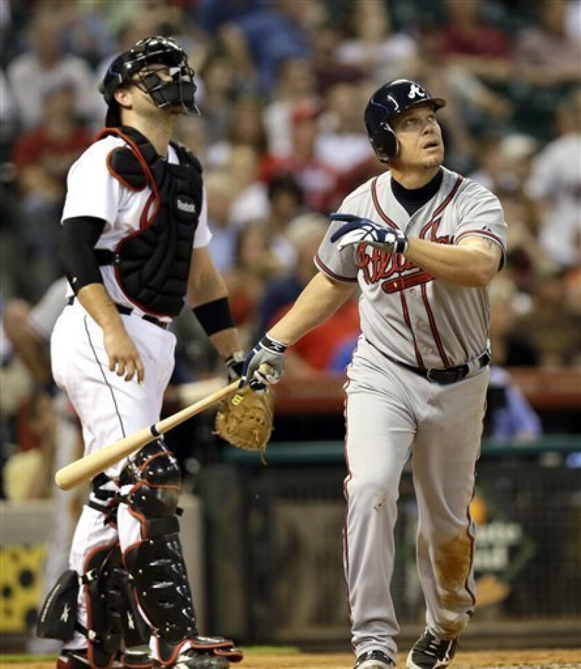 Atlanta Braves' Chipper Jones, right, watches his two-run home run along with Houston Astros catcher Chris Snyder, left, during the third inning of a baseball game Tuesday, April 10, 2012, in Houston. The Braves' Dan Uggla scored on Jones' homer. (AP Photo/David J. Phillip)
