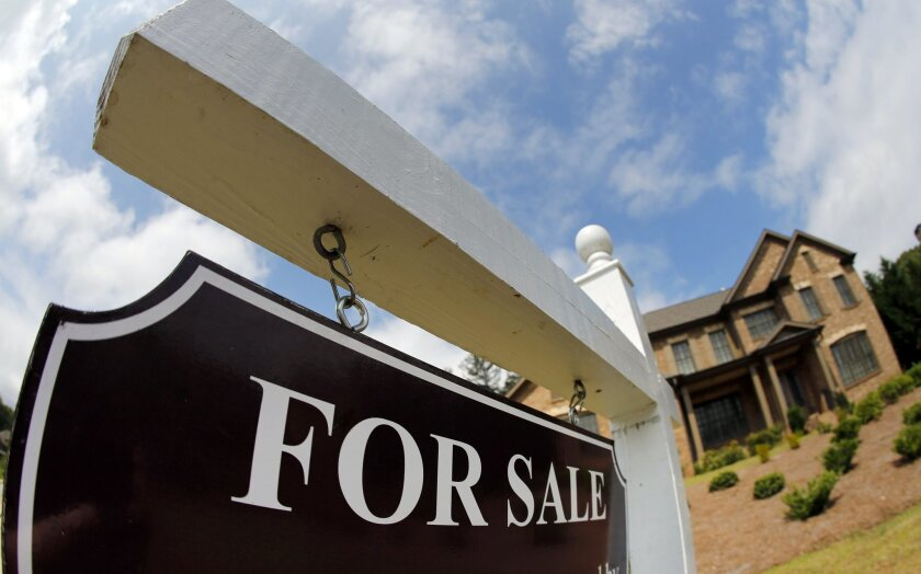 FILE - This June 4, 2015, file photo, shows a sign in front of a home for sale in Roswell, Ga. Three new industry analyses released Thursday, Nov. 5, 2015, show that the recovering economy has produced a divided U.S. housing market. Where people live, their age and the color of their skin have larg