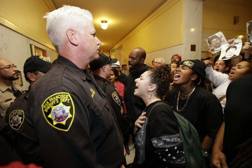 Demonstrators yell at police officers blocking the entrance to a crowded police commission hearing at city hall Wednesday, Dec. 9, 2015, in San Francisco. San Francisco's police chief wants city officials to arm his department with Tasers amid continued protests over the shooting death of Mario Woods, who was wielding a knife when he was shot by police. (AP Photo/Marcio Jose Sanchez)
