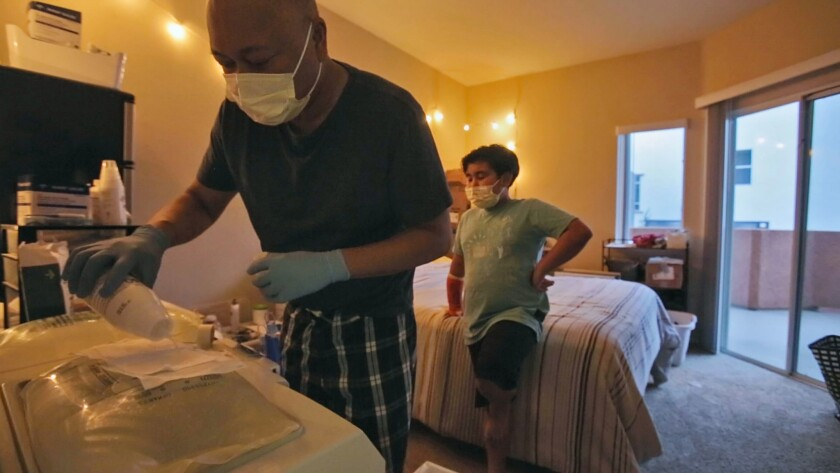 Binh Nguyen and his son Garret prepare the last dialysis treatment the night before his kidney transplant surgery.