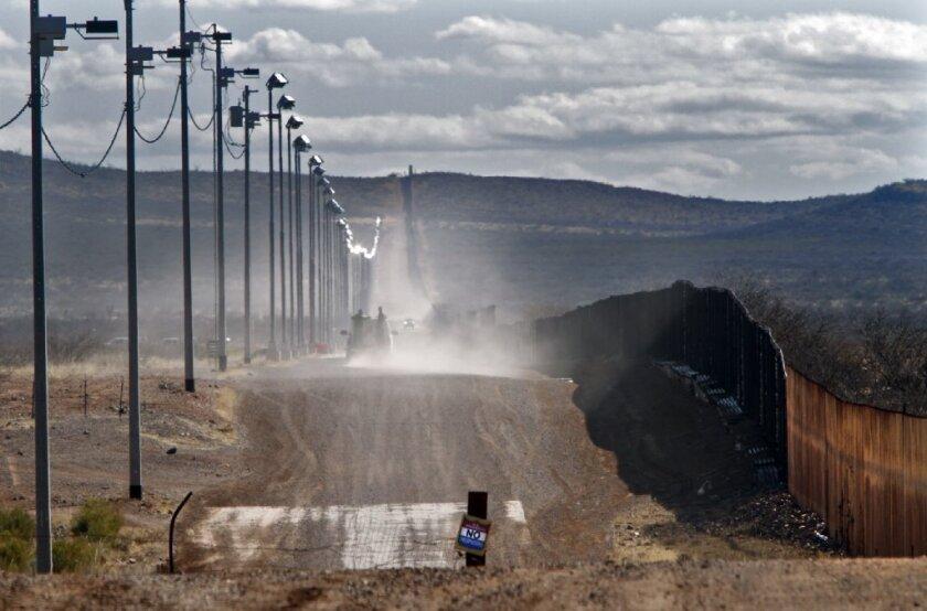 A U.S. Border Patrol vehicle moves along the Mexican border in Naco, Ariz.