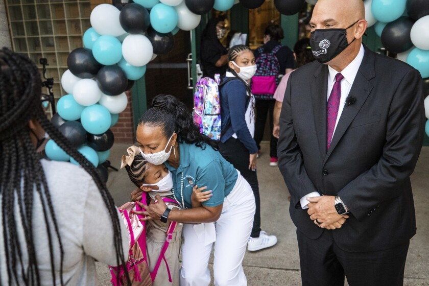 Principal Andrea Harper hugs a student as Harper and Superintendent Kent P. Scribner greet students on the first day of school Monday, Aug. 16, 2021, at T.A. Sims Elementary School in Fort Worth, Texas. (Yffy Yossifor/Star-Telegram via AP)