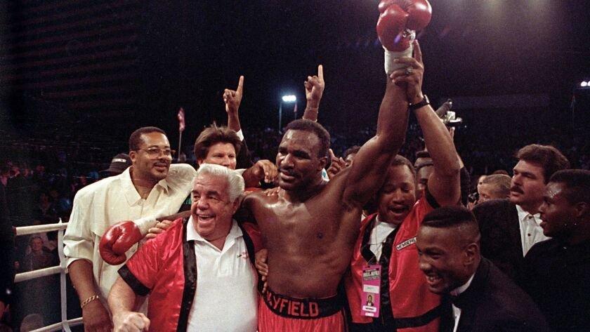 Evander Holyfield drapes his arm around his trainer Lou Duva, left, during celebration in the ring after winning the world heavyweight championship on Oct. 25, 1990.