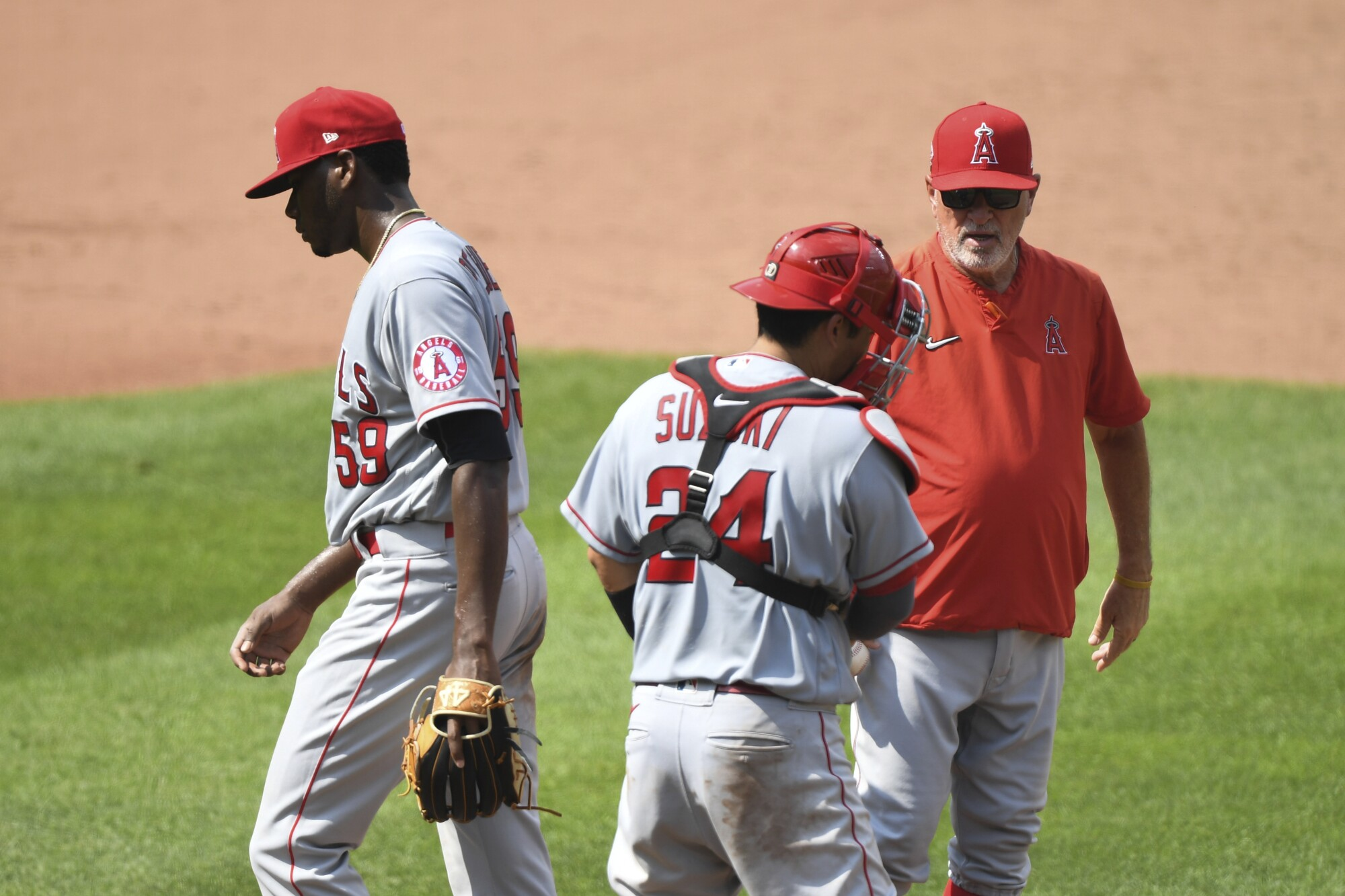 Angels relief pitcher Elvis Peguero is removed from the game by manager Joe Maddon in front of catcher Kurt Suzuki.
