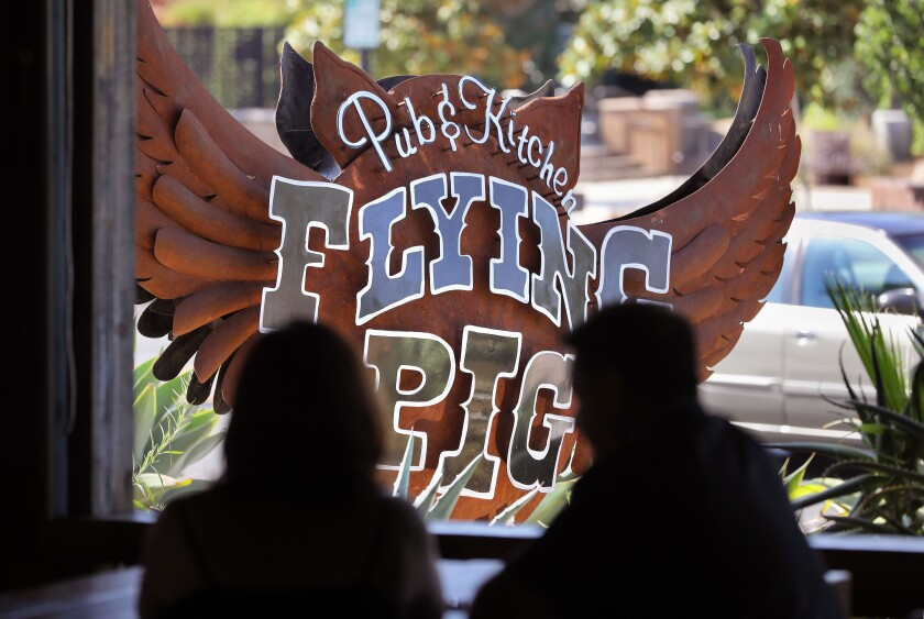 View of the characteristic sign for the Flying Pig Pub & Kitchen on S. Santa Ave. in downtown Vista.