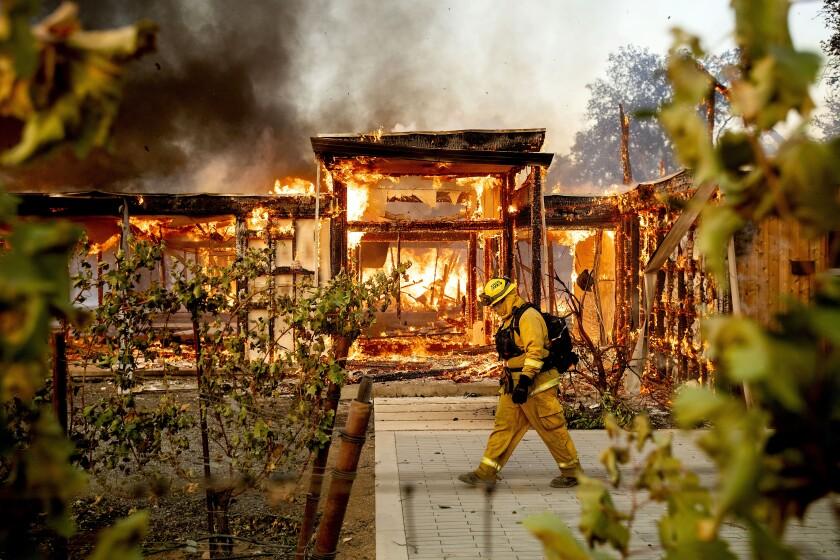 Woodbridge firefighter Joe Zurilgen passes a burning home as the Kincade Fire rages in Healdsburg on Oct 27, 2019.