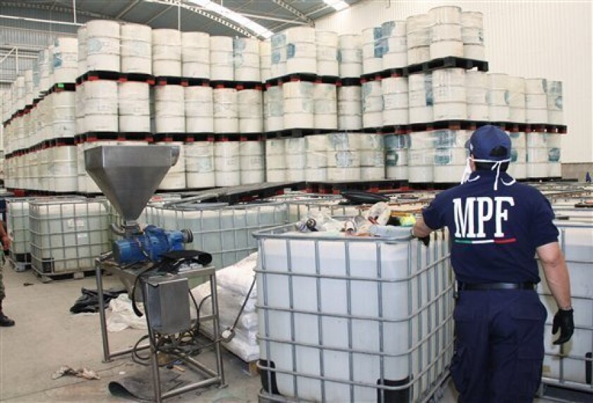 FILE - In this June 20, 2011, photo released by Mexico's Attorney General's office, police from the Federal Public Ministry looks at drums of precursor chemicals for methamphetamine that were seized in Queretaro, Mexico. Mexican drug cartels are flooding U.S. cities with cheap, extraordinarily pure