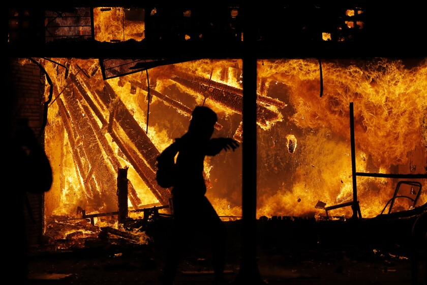 A protester runs in front of the burning  police station May 28 in Minneapolis.