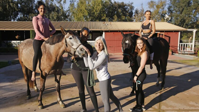 Certified Equine OM instructor Melissa Reese, center, of Spirit Horse Yoga, and stands with Maggie M