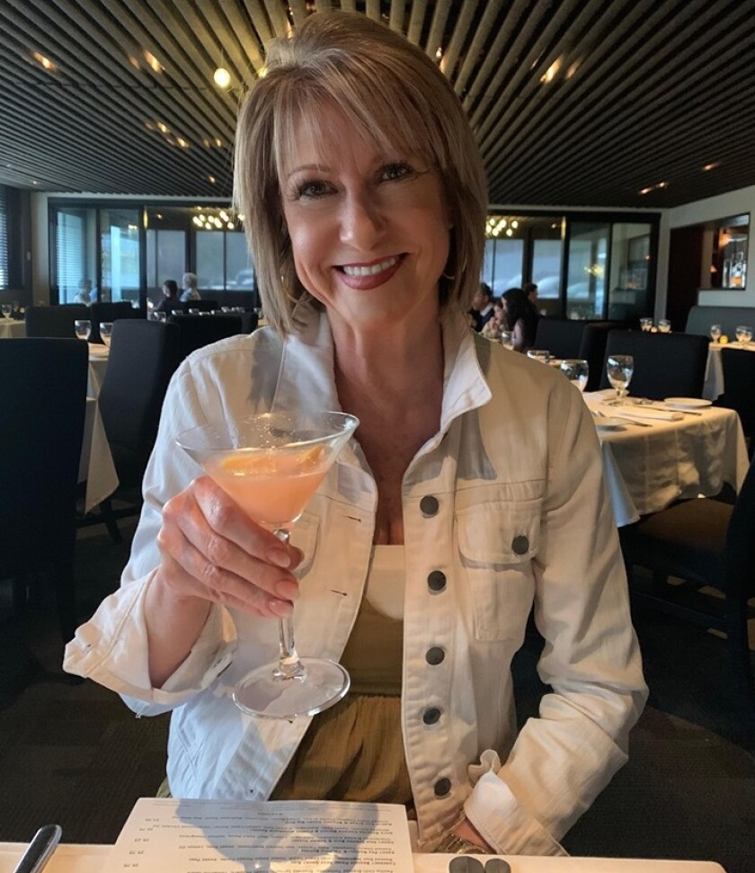 """San Diego attorney Leslie Devaney may look like she is aboard a cruise ship, but she was having her consolation dinner at The Market on March 15 after her 16-day Regent cruise was canceled. Could that be a """"quarantini"""" she is drinking?"""
