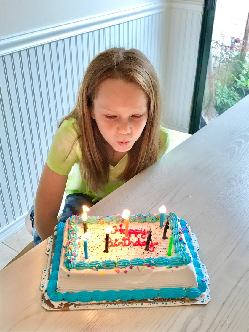 Maizy Tobin blows out the candles on her cake at home.