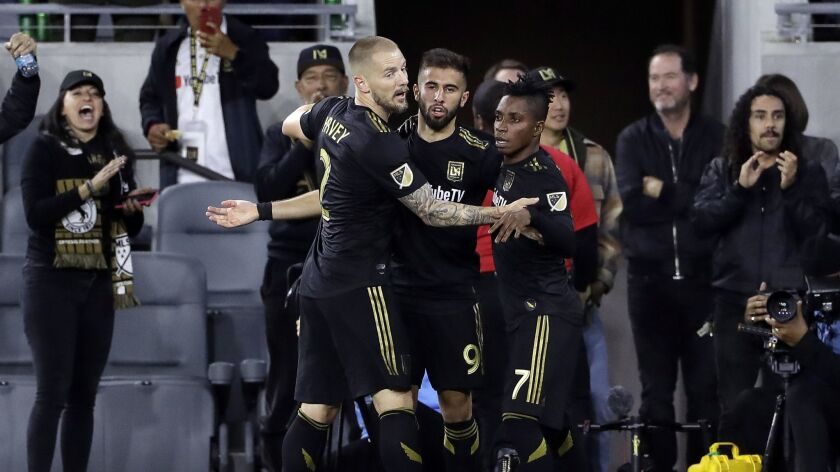 LAFC's Diego Rossi, center, is hugged by teammates Jordan Harvey, left, and Latif Blessing after Rossi's first-half goal against Real Salt Lake on Saturday.