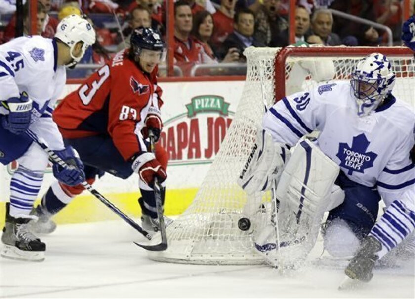 Toronto Maple Leafs defenseman Mark Fraser (45) and Washington Capitals center Jay Beagle (83) work the puck deflected by goalie Ben Scrivens (30) in the first period of an NHL hockey game Tuesday, April 16, 2013 in Washington. (AP Photo/Alex Brandon)