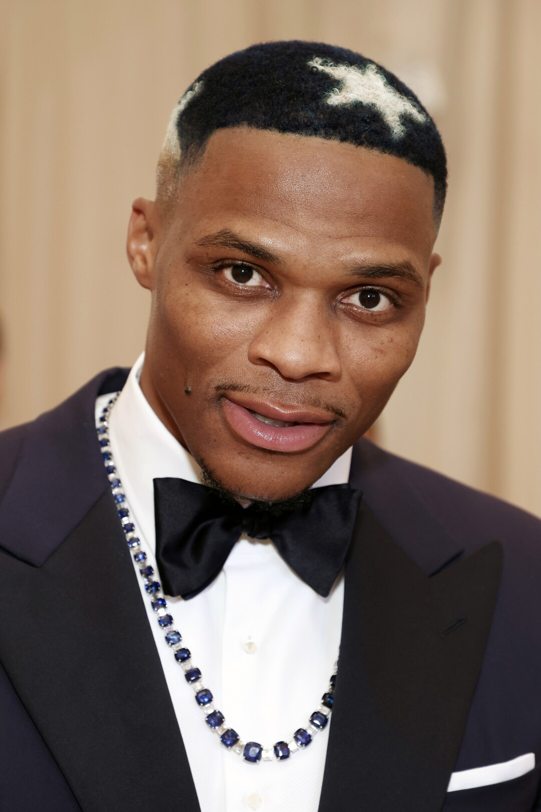 A man in a tuxedo with a star dyed into his hair